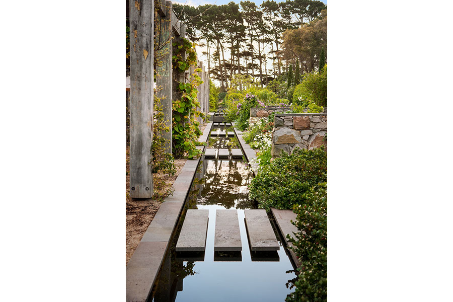 Pergola frames water feature and stone walled garden